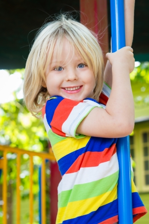 Cute smilling child playing on a pole in a play ground