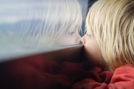 Cute young child deep in thought looking out of a window Stock Photo