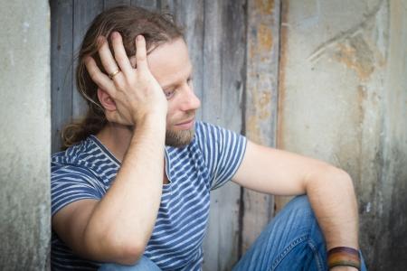 hombre solitario: Primer plano de un hombre deprimido sentado en una antigua puerta Foto de archivo