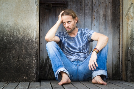 Depressed man sitting alone in a grungy doorway with copy-space  photo