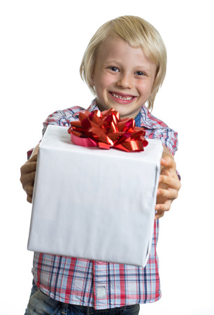 gift giving: Cute, happy child giving a wrapped present. Isolated on white.