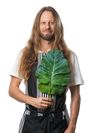 Handsome hippie man holding a kale leaf over his heart as a concept for good health. Isolated on white.