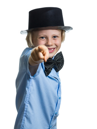 Cute child in top hat and bow tie pointing to camera. Isolated on white.