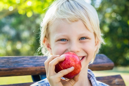 Portrait of a happy child eating a red apple outdoors.