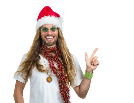 Smiling hippie in Santa hat pointing at copy-space  Isolated on white background Standard-Bild