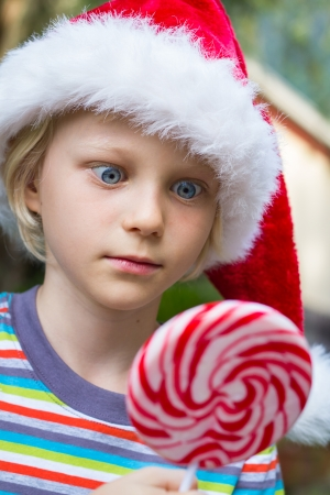 Cute child in Santa hat starring cross-eyed at at a large lollipop photo