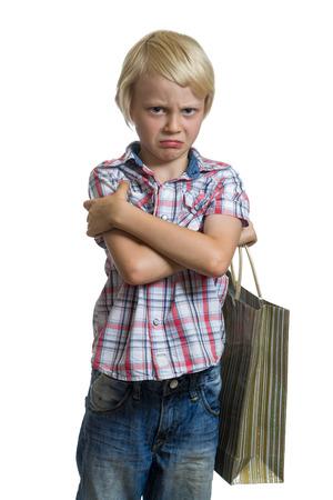 Sulking child holding a gift bag isolated on white background Standard-Bild