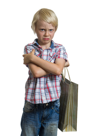 Sulking child holding a gift bag isolated on white background photo