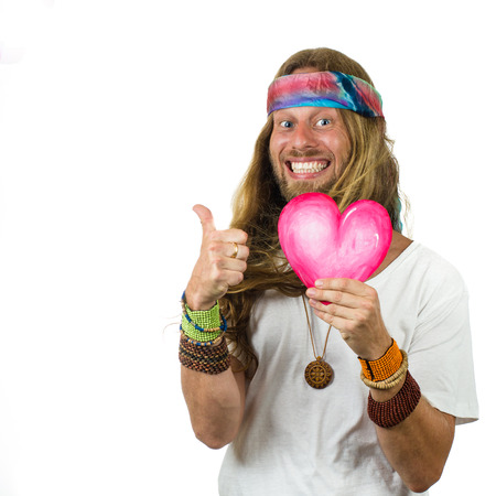 Funny hippie holding a love heart gesturing thumbs up isolated on white Standard-Bild
