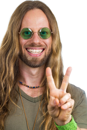 Handsome hippie wearing round green sunglasses doing a peace sign photo