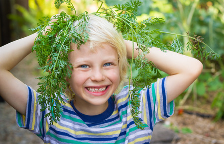 Happy child having playing fun in his vegetable garden, with carrot tops for hair photo