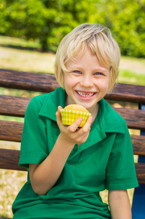 Cute happy school child eating a homemade cupcake outdoors on a park bench photo