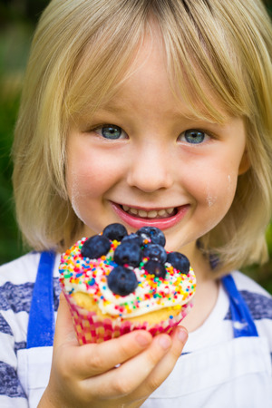 Close-up of cute, smiling child holding a colorful homemade cupcake