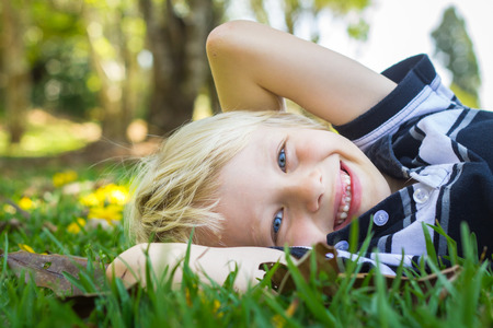 Cute happy child relaxing in park with arms behind his head on the grass