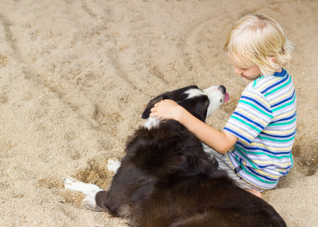 Young boy sitting with arm around his pet dog at the beach Standard-Bild