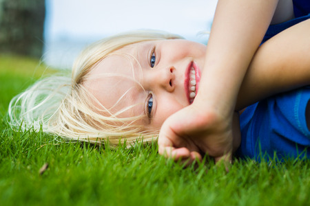 Cute, smiling child lying on the grass