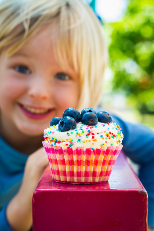 Cute child looking at a delicious cupcake covered in sprinkles and blueberries. Focus is on cupcake Standard-Bild