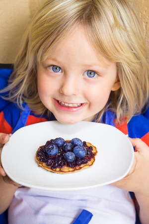Adorable child holding a healthy homemade wholemeal pikelet with fresh blueberries and jam on top Standard-Bild