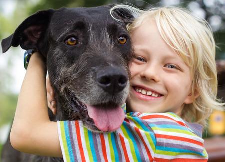 Gelukkige jonge jongen liefdevol knuffelen zijn hond in het park