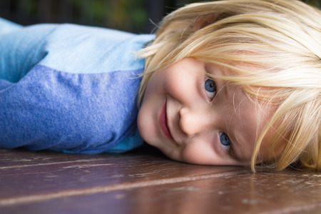 Cute, smiling child lying down looking to camera