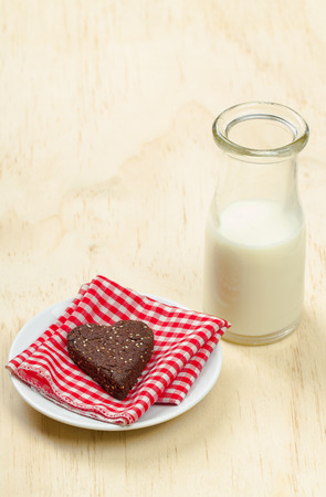 Healthy homemade dark chocolate, almond flour and chia seed cookie with a glass of milk