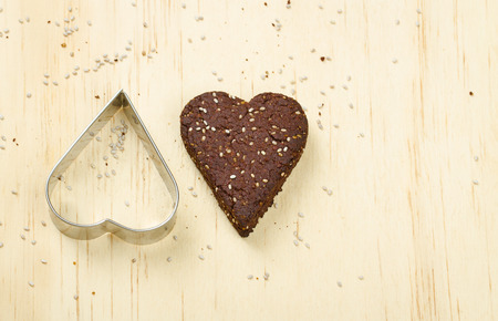 Dark chocolate chia seed love heart cookie and cookie cutter on wooden background