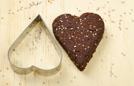 loveheart: Close-up of healthy dark chocolate and chia seed cookies on wooden background with cookie cutter