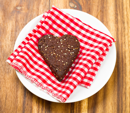 Close-up of dark chocolate and chia seed love heart cookie for healthy snack