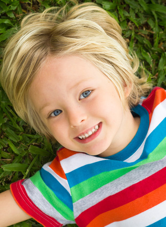 Cute happy child in colorful t-shirt lying on grass Standard-Bild