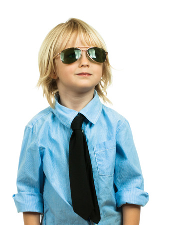 Portrait of a well-dressed cute boy wearing sunglasses and a shirt and tie looking up at copy space. Isolated on white. Standard-Bild