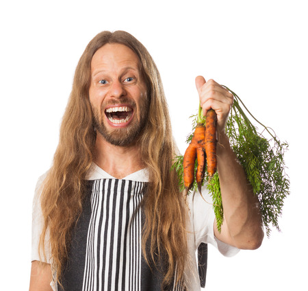 Funny hippie chef holding organic carrots isolated on white
