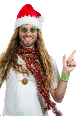 Handsome retro hippie in Santa hat pointing at copy-space. Isolated on white.