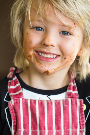 Happy child with messy chocolate face from baking Standard-Bild