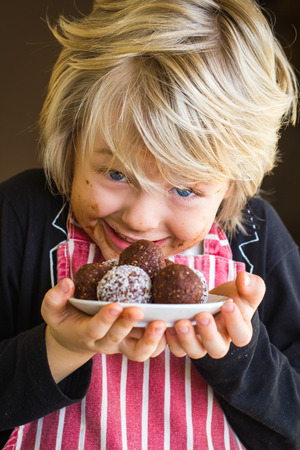 Excited child with messy face showing homemade chocolate balls Standard-Bild