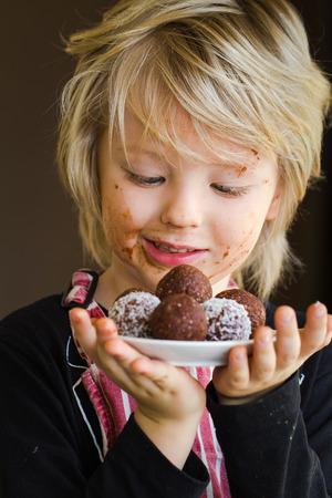 chocolate balls: Cute child holding homemade chocolate balls as a treat