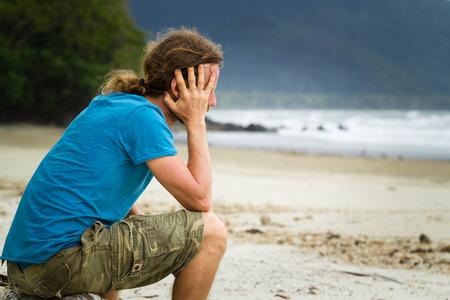 Depressed lonely man sitting at the beach Standard-Bild