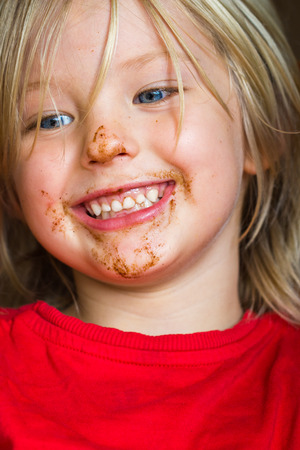 Cute happy child with chocolate covered messy face