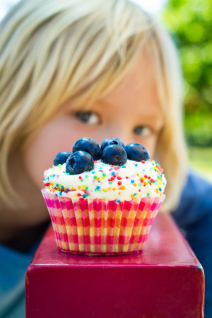 Fat kid: Child looking at colorful tempting cupcake treat. Cupcake is in focus.