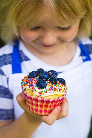 Cute child in apron holding homemade cupcake, focus on cupcake Standard-Bild