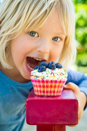맛있는 컵 케이크에 물린하는 방법에 대한 귀여운 자식입니다. 먹고 초점입니다. 스톡 콘텐츠
