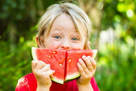 Grappig gelukkig kind het eten van watermeloen buiten het maken van een glimlach
