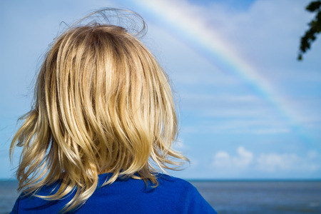 Young child watching a rainbow over the ocean