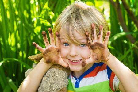 Child playing in garden with dirty hands Stockfoto