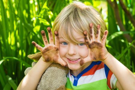 manos sucias: Niño que juega en el jardín con las manos sucias Foto de archivo