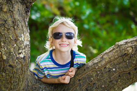 Happy child in sunglasses leaning over tree next to beach