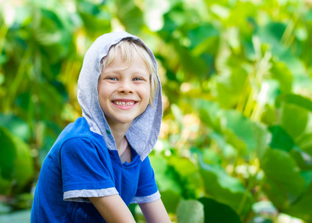 Portait of a smiling, healthy child out in nature next to a lilly pond