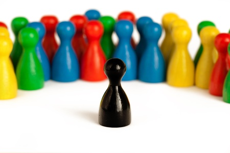 single black game figurine in front of a group of other figurines, symbolizing the concepts of identity, belonging, integration, but also leadership  photo