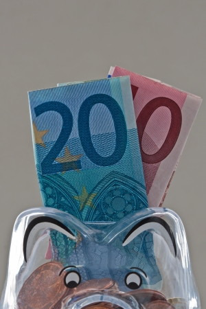 Translucent piggy bank filled with Euro notes and coins Stock Photo - 20259431