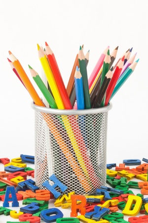 many colored pencils in a holder before white background and surrounded by colorful wooden letters photo