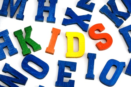 Word kids made from colorful wooden letters on white background  Stock Photo - 21627595